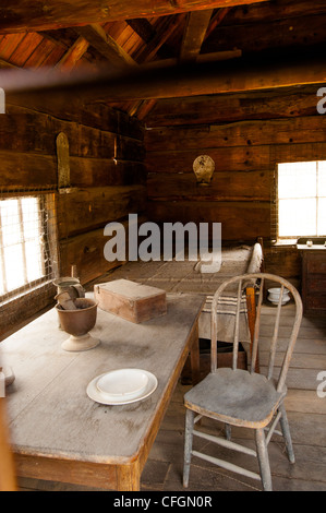 Interior of 19C Mormon log cabin in the Marshall Discovery State Park in Gold Rush country of Coloma Northern California - Stock Photo