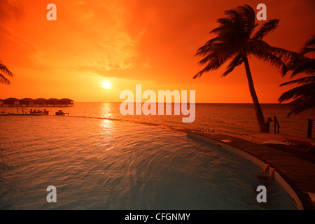 Sunset over the swimming pool, Filitheyo island, Maldives - Stock Photo