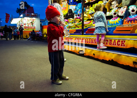 A small boy eats candy and watches a clown game in a fair side show. - Stock Photo