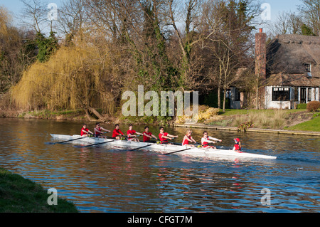 Rowing team go past picturesque thatched cottage at Fen Ditton, Cambridgeshire, England. - Stock Photo