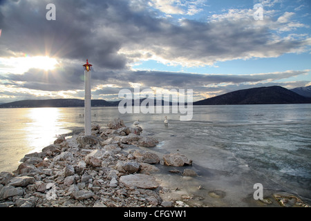 lighthouse in frozen lake - Stock Photo