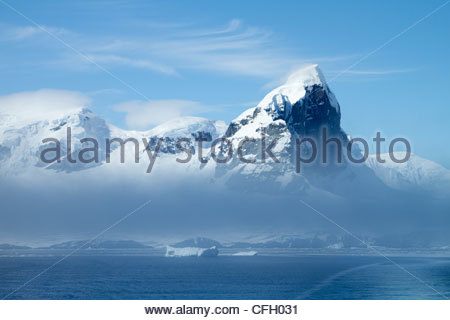 A glacier pushes through rugged terrain to end at the sea. - Stock Photo