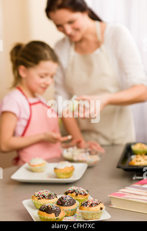 little girl taste sprinkles decorating cupcakes with mother at home stock photo