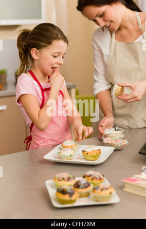 Woman Decorating Cupcakes woman and little girl make cupcakes together fill baking form