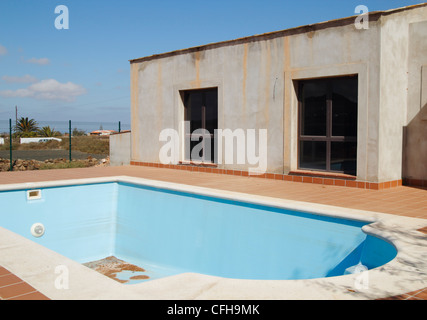 Empty swimming pool next to house at unfinished/abandoned building site in the Canary islands, Spain - Stock Photo