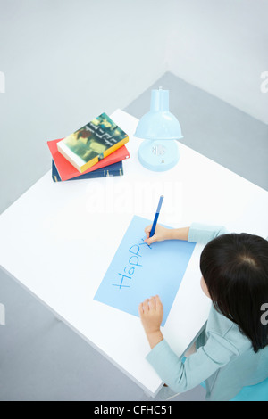 A girl writing 'Happy' on the blue paper with a blue colored pencil - Stock Photo
