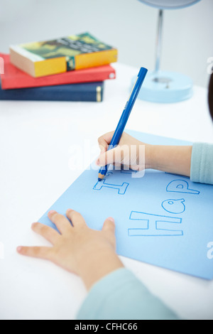 A girl writing 'I'm happy' on the blue paper with a blue colored pencil - Stock Photo