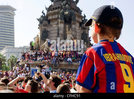 A young boy Barcelona FC fan in a Ibrahimovic strip sits in a crowd of people awaiting for the team to parade the - Stock Photo