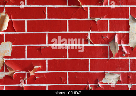 Old wall painted in a brick pattern with flaky paint - Stock Photo
