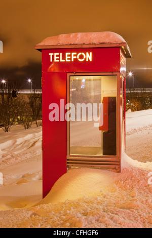 Norwegian telephone box buried in a snow drift Tromso Troms North Norway Scandinavia Europe - Stock Photo