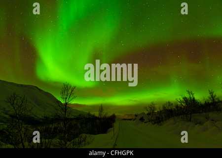 Aurora borealis or northern lights seen over a snow covered road, Troms, North Norway, Europe - Stock Photo