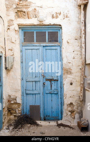 Old wooden double blue door with peeling paint in Marpissa, on the Greek Cyclade island of Paros. - Stock Photo