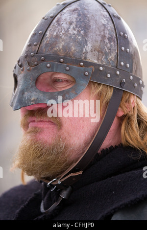 Bearded Icelander Viking re-enactor wearing face Helmet and carrying sword at the 27th Annual JORVIK Festival in - Stock Photo