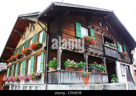 Swiss wooden chalet with window plants - Stock Photo