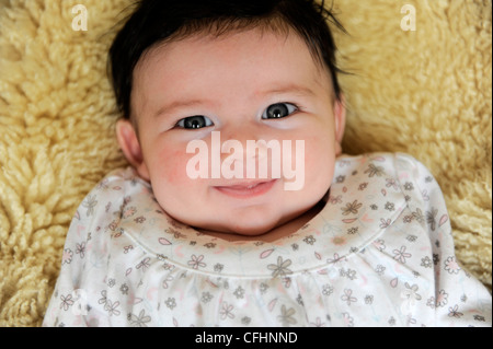 Gorgeous baby girl lying on sheepskin looking happy relaxed and smiling - Stock Photo