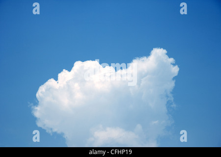 A single white cumulus cloud in a blue sky. - Stock Photo