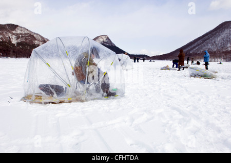 Fishermen ice fishing on Haruna Lake in Gunma Japan - Stock Photo