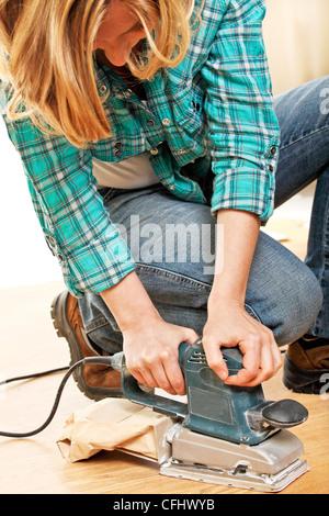 woman use electric sander on wood floor - Stock Photo