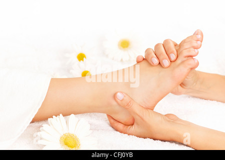 Female hands giving massage to soft bare foot - Stock Photo