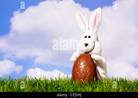 Fun photo of a white easter bunny puppet holding a large chocolate egg on grass with a blue cloudy sky background. - Stock Photo