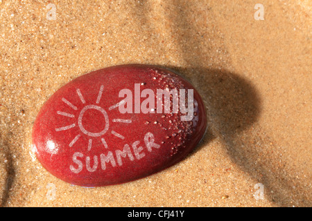 Concept photo of a wet red pebble on a sandy beach with a drawing of the sun and the word summer on it - Stock Photo