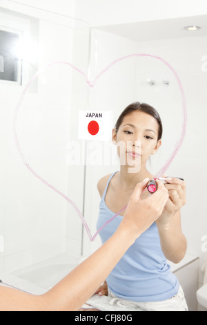 Young woman drawing heart with lipstick on mirror - Stock Photo