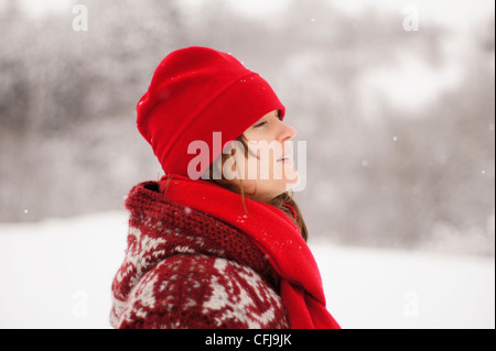 Beautiful young girl with red hat and scarf enjoying the falling winter snow - Stock Photo