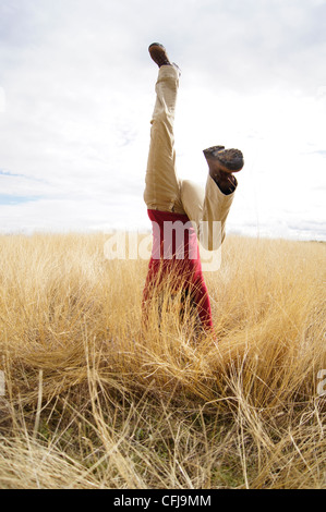 Young girl doing headstand in a filed of long grass - Stock Photo