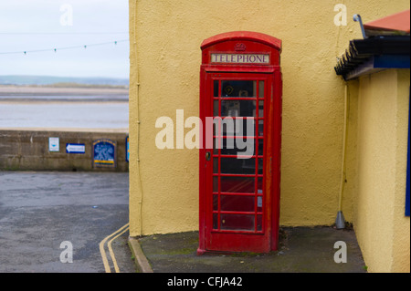 A traditional red telephone box in the Devon village of Appledore next to the waterfront. - Stock Photo