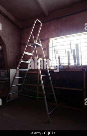 Ladder in a workshop or small old factory interior - Stock Photo