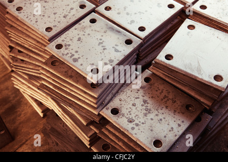 Grunge rusty rectangle metal plates with round holes placed on wooden textured board - Stock Photo