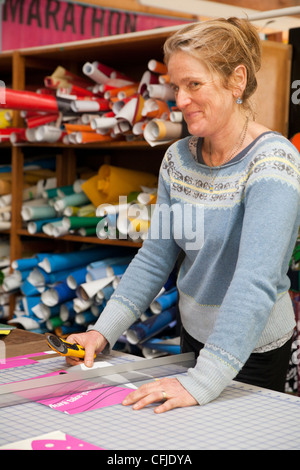 Seamstress recycling trade show banner vinyl into new products with zero waste - Stock Photo