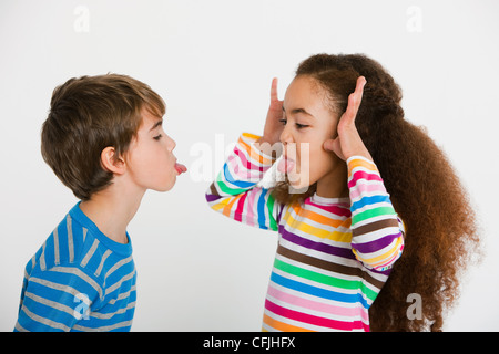 Children making faces at each other - Stock Photo