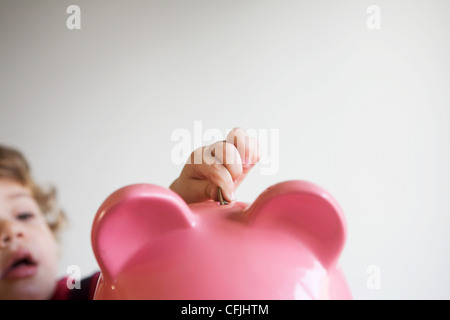 Little boy putting money in piggy bank - Stock Photo