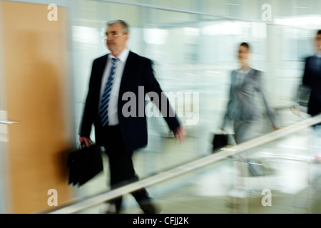 Businessman going along corridor with walking people on background - Stock Photo