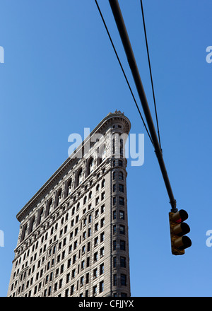 The famous Flatiron building and an overhead traffic light on a sunny day, New York, USA - Stock Photo