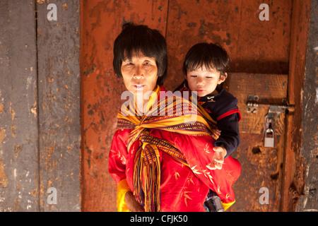 Local woman with child on her back, Wangdue Phodrang (Wangdi), Bhutan, Asia - Stock Photo