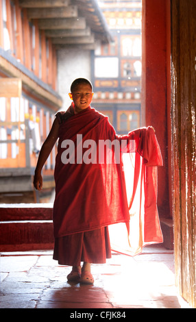 Young Buddhist monk in red robes backlit by evening sunlight at the Jakar Dzong, Jakar, Bumthang, Bhutan, Asia - Stock Photo