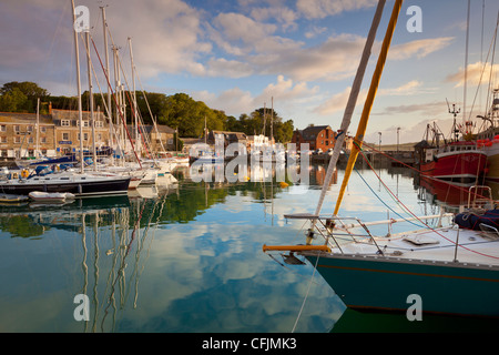 Low morning light and sailing yacht reflections at Padstow Harbour, Cornwall, England, United Kingdom, Europe - Stock Photo