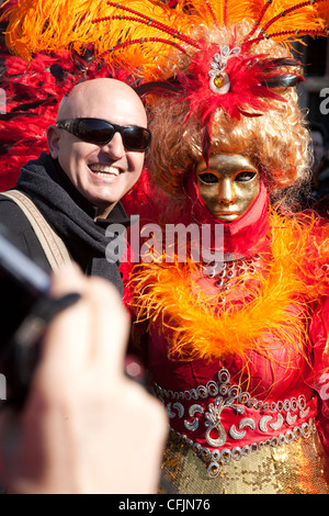 Tourist having his picture taken with a carnival character at the Venice Carnival 20121, St Marks Square Italy - Stock Photo