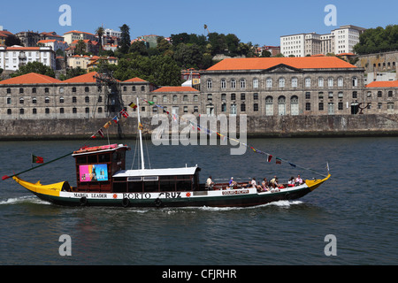 A wooden barcos rabelos boat, once used of delivering wine casks, cruises on the River Douro at Porto, Douro, Portugal, - Stock Photo