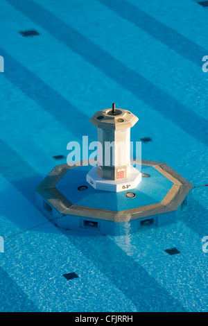 Diving platform surrounded by blue diagonal stripes seen through the clear dappled water in Tinside Lido swimming - Stock Photo