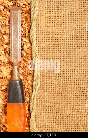 Old steel chisel on Sawdust flakes piled on logs of sack - Stock Photo