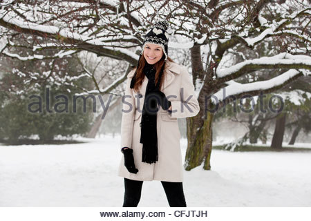 A young woman standing in the snow, smiling - Stock Photo