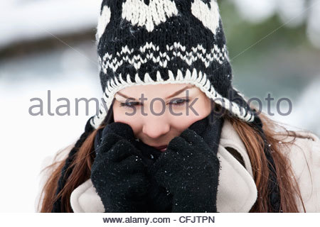 Portrait of a young woman wearing a woolen hat, keeping warm - Stock Photo
