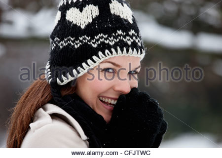 Portrait of a young woman wearing a woolen hat, trying to keep warm - Stock Photo