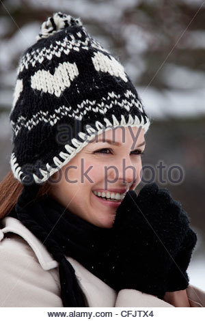 Portrait of a young woman wearing a woollen hat, trying to keep warm - Stock Photo