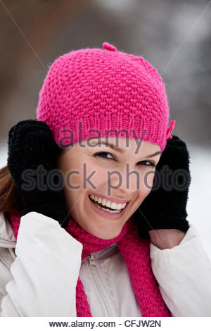 A young woman putting on a pink woolen hat - Stock Photo