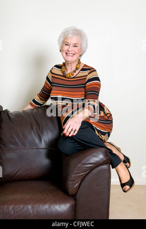 Attractive senior lady sat on edge of leather sofa smiling and looking relaxed - Stock Photo