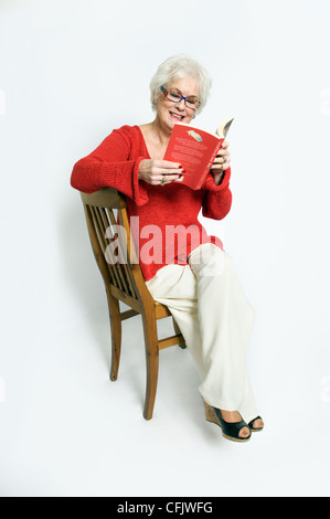 Attractive senior lady in bright clothing sat on chair reading book taken against a white background - Stock Photo